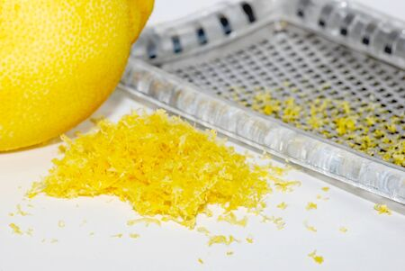 grater: Small heap of grated lemon zest with a whole lemon and grater