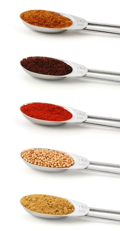 Spices measured in metal teaspoons, isolated on a white background  chinese five spice, ground cloves, smoked paprika, mustard seeds, ground cumin  photo