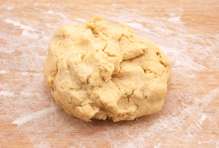 pliable: Fresh ball of pastry ready to be rolled out on a floured wooden board Stock Photo