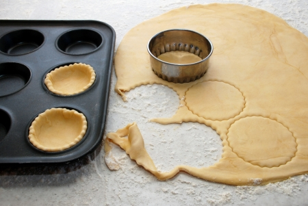 jam tarts: Circles being cut from fresh pastry to and filling a bun tin to make jam tarts Stock Photo