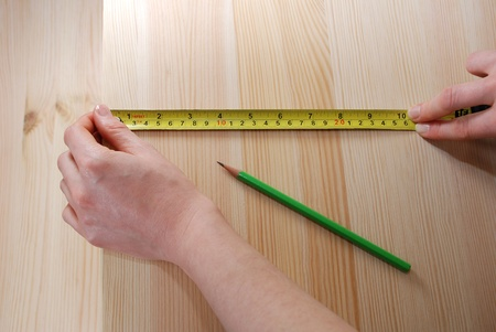 centimetres: Two hands measuring a wooden board with a steel tape measure in inches and centimetres