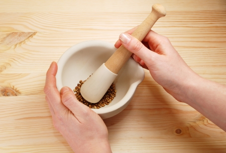 A woman uses a pestle and mortar on a wooden table to crush whole coriander seeds photo