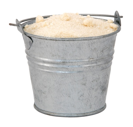 caster: Golden caster sugar in a miniature metal bucket, isolated on a white background