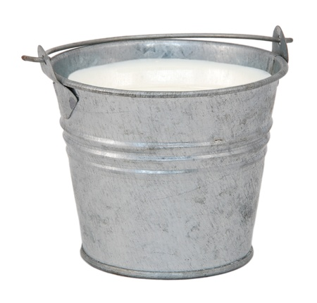 Milk in a miniature metal bucket, isolated on a white background photo