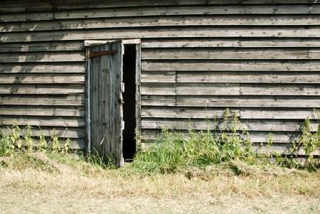 ajar: Rustic wooden farm hut with the door ajar