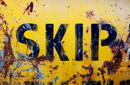 dumpster: The side of a rusty industrial skip or dumpster with peeling yellow paint