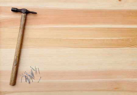 Hammer and metal nails on a woodgrain background Stock Photo - 22550941