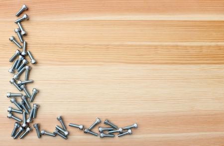 Socket head bolts as L-shape border on woodgrain background