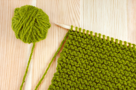 Green ball of wool and garter stitch on a knitting needle, on wooden table photo
