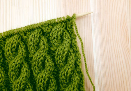 cable stitch: Green coiled rope cable knitting stitch on the needle, on a wooden background Stock Photo