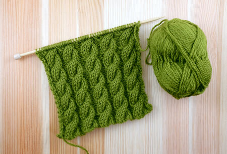 cable stitch: Rich green coiled rope cable stitch knitting with a ball of wool on woodgrain Stock Photo