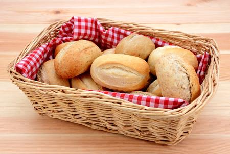 Wicker basket full of crusty bread rolls on a wooden table photo