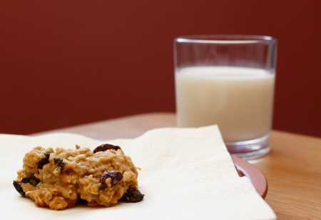 Closeup of a freshly baked oatmeal raisin cookie with a glass of milk photo