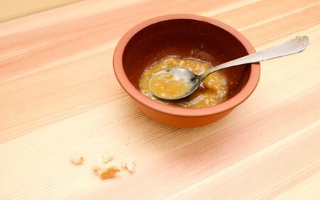 emptied: Emptied bowl of vegetable soup with bread crumbs on the table