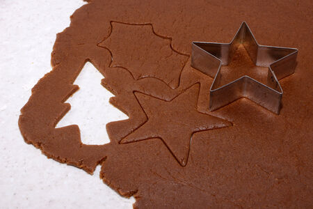 gingerbread cookie: Festive shapes and star cookie cutter on gingerbread cookie dough