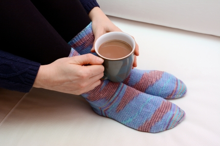 tea cosy: Woman holding a cup of tea or coffee, wearing warm winter socks