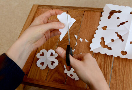 Woman making paper snowflakes with scissors at a wooden craft table photo