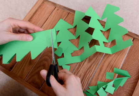 Cutting green card with scissors to make a chain of Christmas trees photo