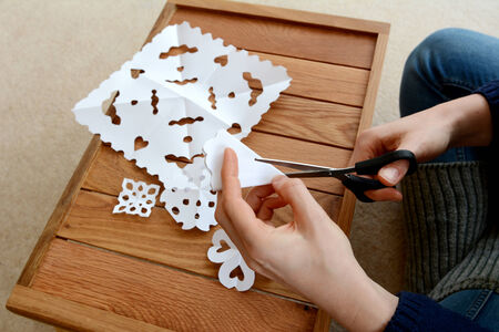 Woman using scissors to cut folded white paper into snowflake designs photo