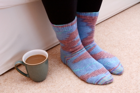 Cup of hot tea or coffee on the floor by a woman photo