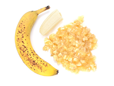 Spotty, overripe banana with whole and mashed fruit, isolated on a white background photo