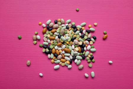 Mixed dried beans - black turtle beans, flageolet beans, pinto beans, brown beans, haricot beans, green split peas and yellow split peas - on a pink background photo
