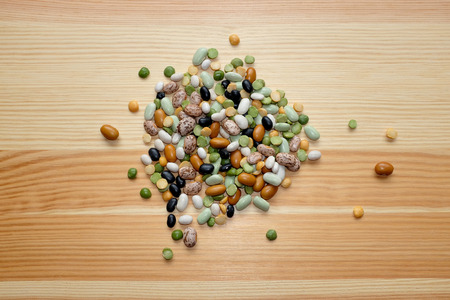 Mixed dried beans - black turtle beans, flageolet beans, pinto beans, brown beans, haricot beans, green split peas and yellow split peas - on a wooden background photo