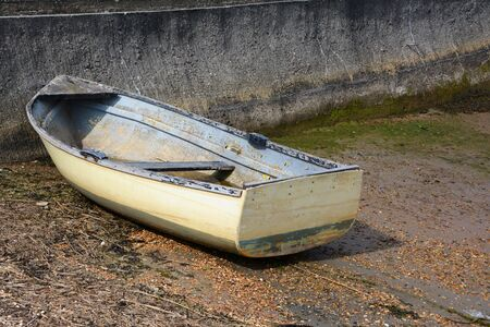 slipway: Weather-beaten white and blue dinghy with peeling paint, out of water on a concrete slipway Stock Photo
