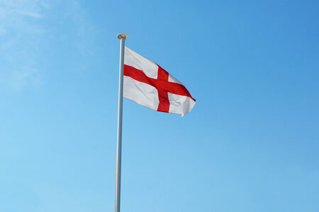 The English national flag, the St Georges Cross, flying against a blue sky