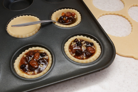 mincemeat: Filling mince pies with mincemeat, pastry scraps beyond Stock Photo