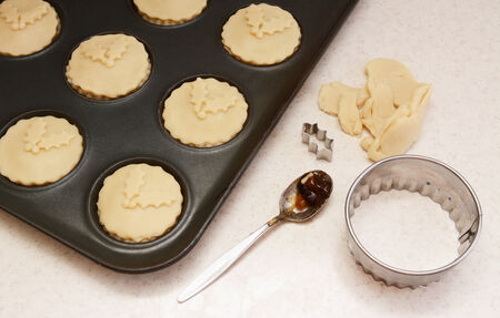 Uncooked mince pies in a bun tin, pastry leftovers, teaspoon and cutters photo