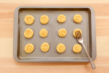 cookie sheet: Flattening a tray full of balls of cookie dough with a metal fork Stock Photo