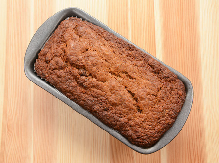 Freshly baked banana loaf in a lined tin on a wooden table photo