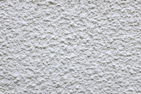 Wall of rough cement render painted white as an abstract background texture