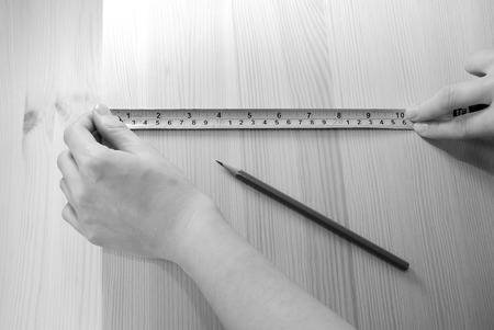 centimetres: Two hands measuring a wooden board with a steel tape measure in inches and centimetres - monochrome processing