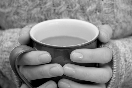Two hands keeping warm, holding a hot cup of tea or coffee - monochrome processing photo