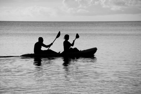black white kayak: Man and woman silhouetted at sea in a kayak - monochrome processing