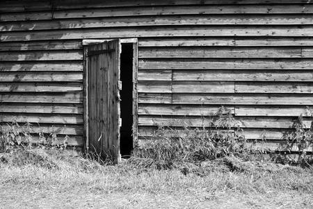 ajar: Rustic wooden farm hut with the door ajar - monochrome processing