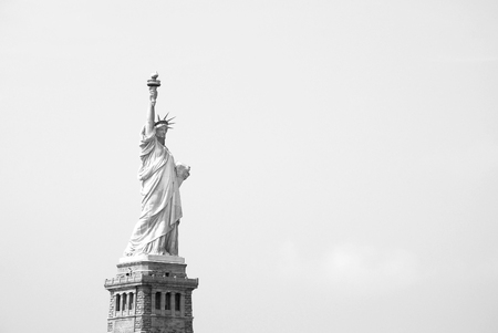 The Statue of Liberty stands proudly against a clear sky - monochrome processing photo