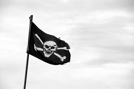 Ragged pirate flag with skull and crossbones flying from flagpole - monochrome processing 版權商用圖片