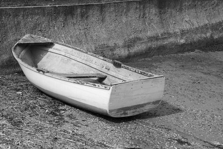 slipway: Weather-beaten dinghy with peeling paint, out of water on a concrete slipway - monochrome processing Stock Photo