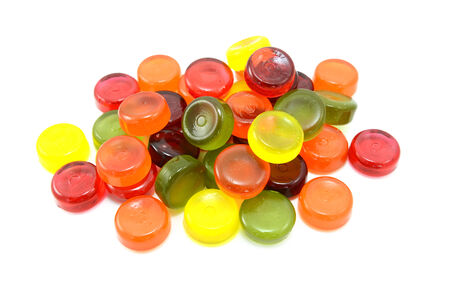 Pile of multi-coloured boiled sweets or hard candies, isolated on a white background photo