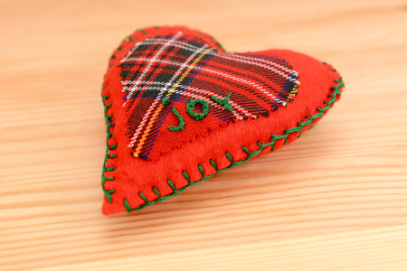 Close-up of handmade festive pomander, embroidered with the word JOY, on a wooden table photo