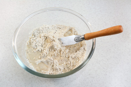 palette knife: Combining water and bread flour mix with a flat-bladed palette knife