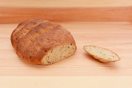 malted: Fresh multi seed malted bread loaf with the crust cut off on a wooden surface