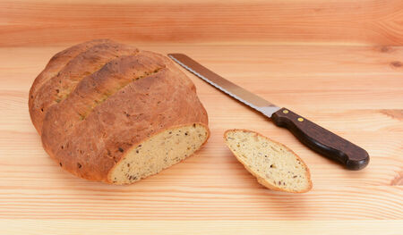 bread knife: Freshly baked loaf of bread with the first slice taken and a bread knife on the table Stock Photo