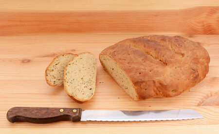 bread knife: Bread knife with slices of bread cut from a seeded loaf of bread