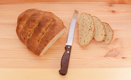 pine three: Fresh loaf of bread with a sharp knife and three cut slices on a pine table