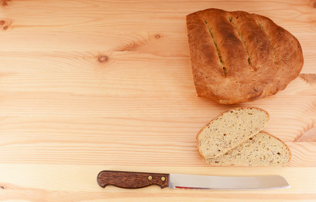 bread knife: Fresh loaf of bread, cut slices and bread knife form a border with copy space Stock Photo