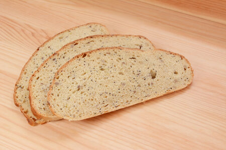 pine three: Three slices of multi seed malted bread on a pine wood table